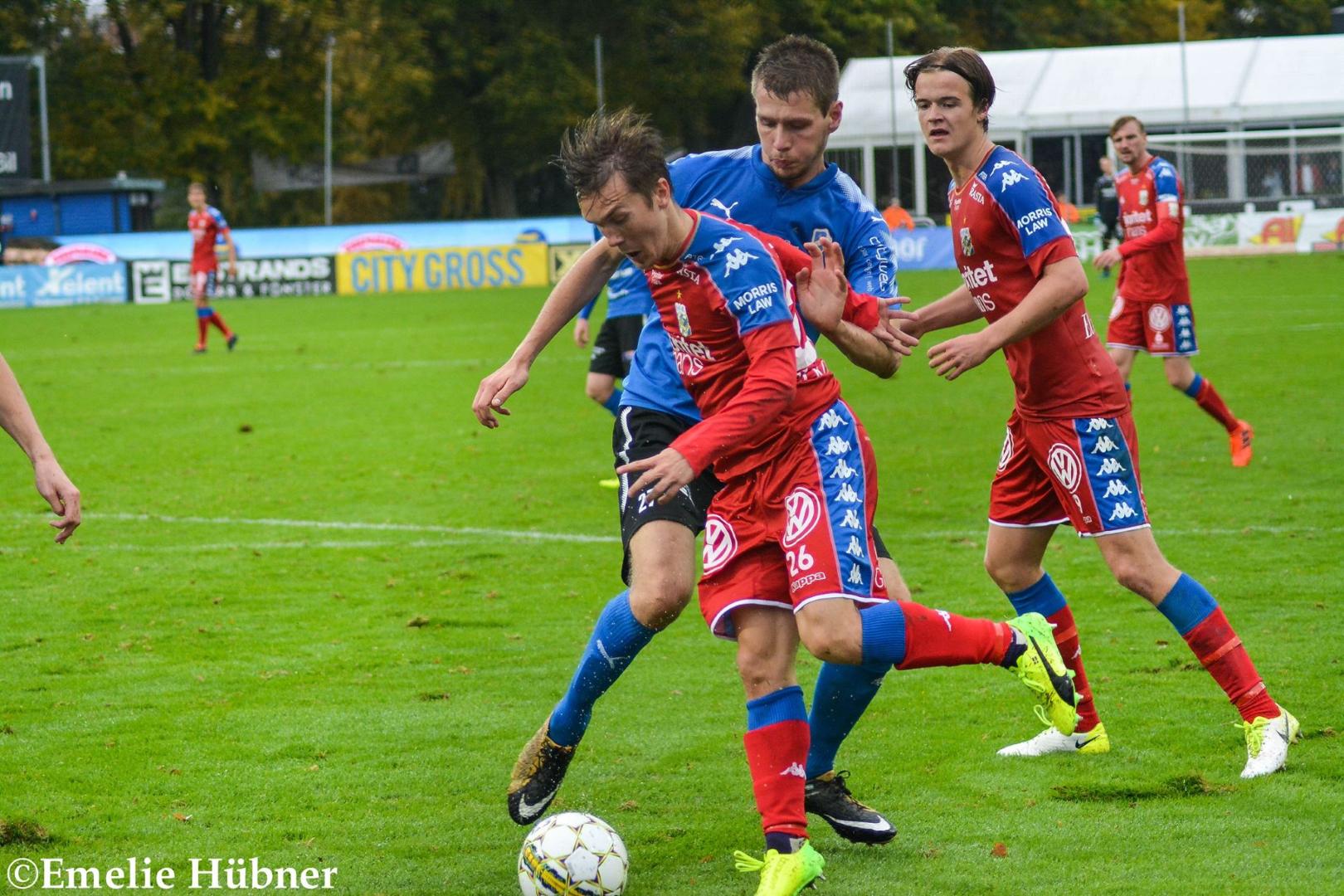 Patrik Karlsson Lagemyr och August Erlingmark på varsin sida om en HBK-spelare. I bakgrunden till höger ses Sebastian Eriksson.